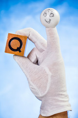 Finger puppet holding wooden cube with capital letter Q