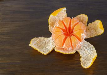 Peeled mandarin orange on the wooden background