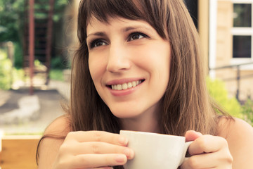 Portrait of young smiling woman in cafe