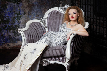 beautiful red-haired girl in evening dress sitting