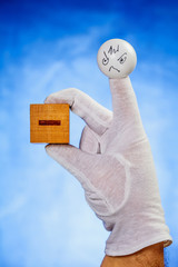 Finger puppet holding wooden cube with minus sign