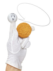 Smiling finger puppet with talking bubble holds oatmeal cookie