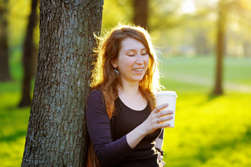 Young woman with coffee outdoors