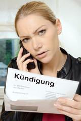 Frau telefoniert entsetzt wegen Kündigung