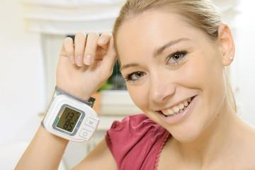 Frau mit Blutdruck-Messgerät an Handgelenk