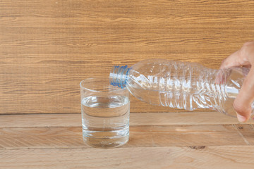 water from bottle in glass on wood background