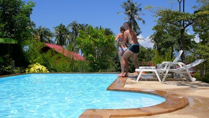 Young Fun Couple Jumping into Swimming Pool. Slow Motion.