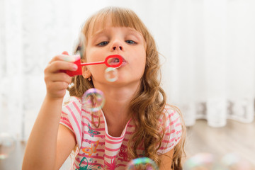 Little girl playing at home with bubble blower.