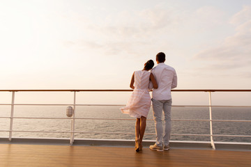 young couple standing on ship deck during sunset