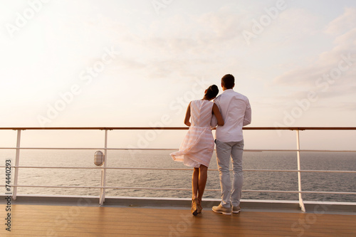 canvas print picture young couple standing on ship deck during sunset