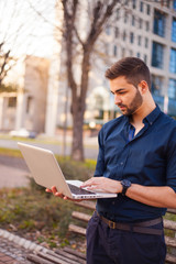Businessman corresponding through internet by office building