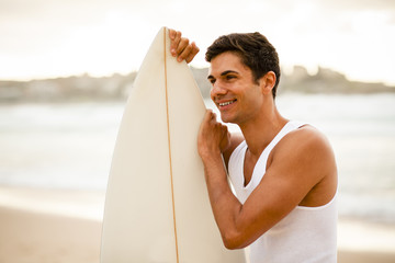 Young surfer standing with his surfboard