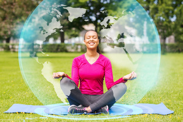 smiling woman meditating on mat outdoors