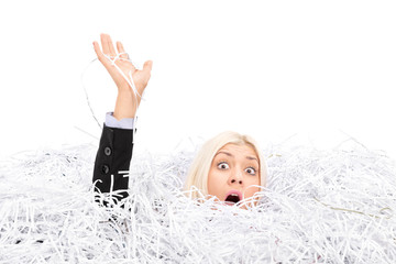 Businesswoman drowning in a pile of shredded paper