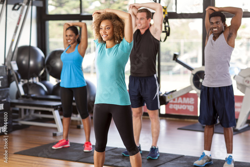Poster Fitness Multi-ethnic group stretching in a gym