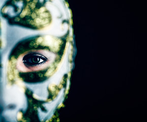 woman in masquerade mask at black background