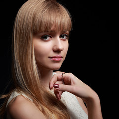 Beautiful long blond hair woman looking on black background