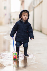 real portrait of a child playing in the street on a rainy day