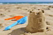 sandcastle and toy shovels on the sand of a beach - 74447669