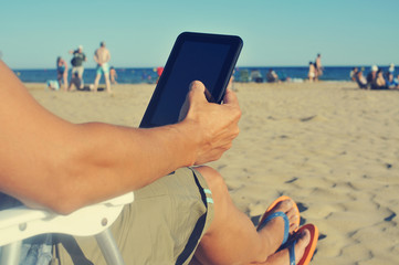 young man using a tablet on the beach