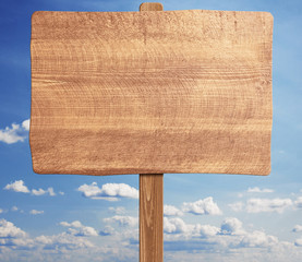 Brown wooden signpost against blue sky.
