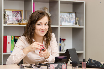 Girl on office work delves into cosmetics
