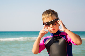 Kid in his diving suit and glasses at the beach