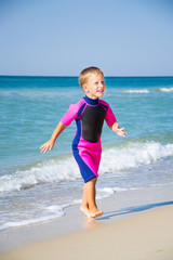 kid in his diving suit leaving water at the beach