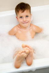 Cute three year old boy taking a bath with foam