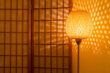 decorative lamp in front of a wooden screen