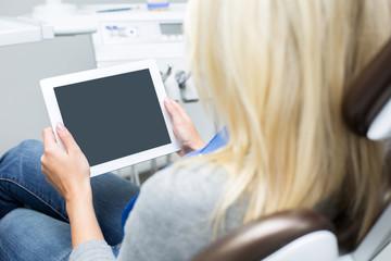 Junge Dame in Zahnarztstuhl schaut auf Tablet