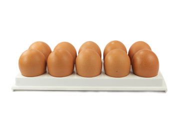 brown hen's eggs in egg flat isolated over white