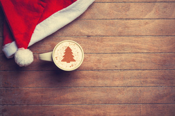 Cappuccino with christmas hat on wooden table.