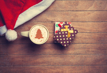 Cappuccino with christmas hat and gift on wooden table.