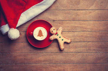 Cappuccino with christmas hat and gingerbread man on wooden tabl