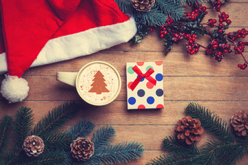 Cup of coffee and gift box with pine and hat on wooden table.