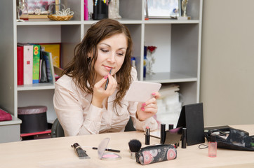 Young girl in the office is painted with lipstick
