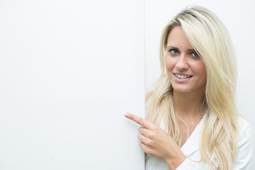 Junge Dame neben weißer Wand mit Platz für Text