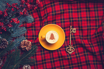 Cappuccino and pine branch  with key on tartan background