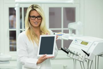 Junge Dame Zahnarzt Helferin hält Tablet vor Zahnarzt Stuhl
