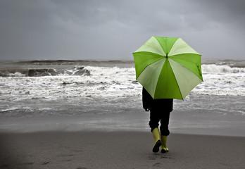 Niño bajo la lluvia en la playa con paraguas