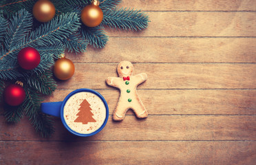 Cappuccino with gingerbread man and pine branch on wooden table.