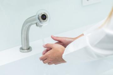 Junge Dame wäscht sich die Hände im Kittel unter Wasser