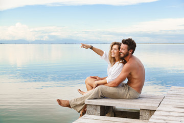 Smiling Couple sitting on a jetty and pointing to the horizon