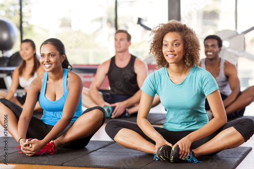 Tuinposter Gymnastiek Multi-ethnic group stretching in a gym