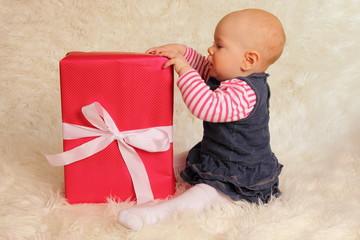 Baby sitzt neben Geschenk
