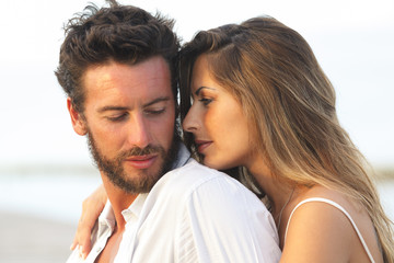 woman embracing her man from behind on seaside background