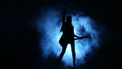 Silhouette of a young girl playing on electric guitar.