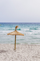 Straw umbrella on sand beach.
