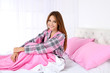 Young beautiful woman sitting on bed